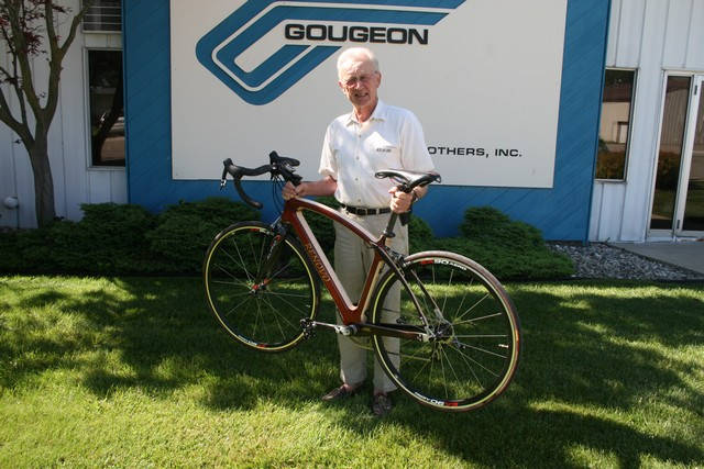 Meade Gougeon shows off his lightweight Renovo Hardwood Bicycle. The custom bike is made of curly maple outlined with a pinstripe of wenge. The outer laminate is padauk. The stays' outer layers are wenge with centers of Port Orford cedar.