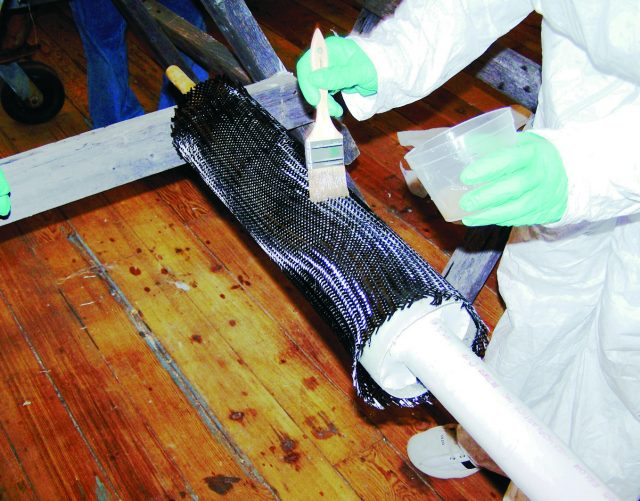 Wetting out the carbon fiber layer with epoxy.