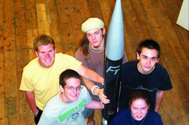 "The Flying Tigers rocket team with their finished 8' 4"" rocket. From bottom left, clockwise: James Roesner, Richard Lester, Brad Parker, Kyle Smith and Brett Cockerill."