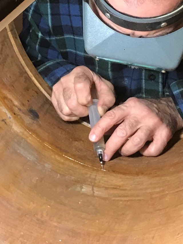 Injecting WEST SYSTEM Epoxy into the crack in the drum.