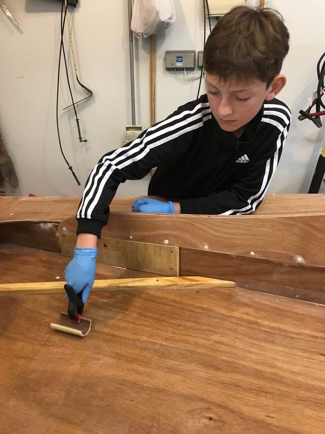 Joshua tips the epoxy coating with a section of foam roller.