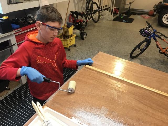 Rolling wet epoxy onto the fiberglass reinforcement.
